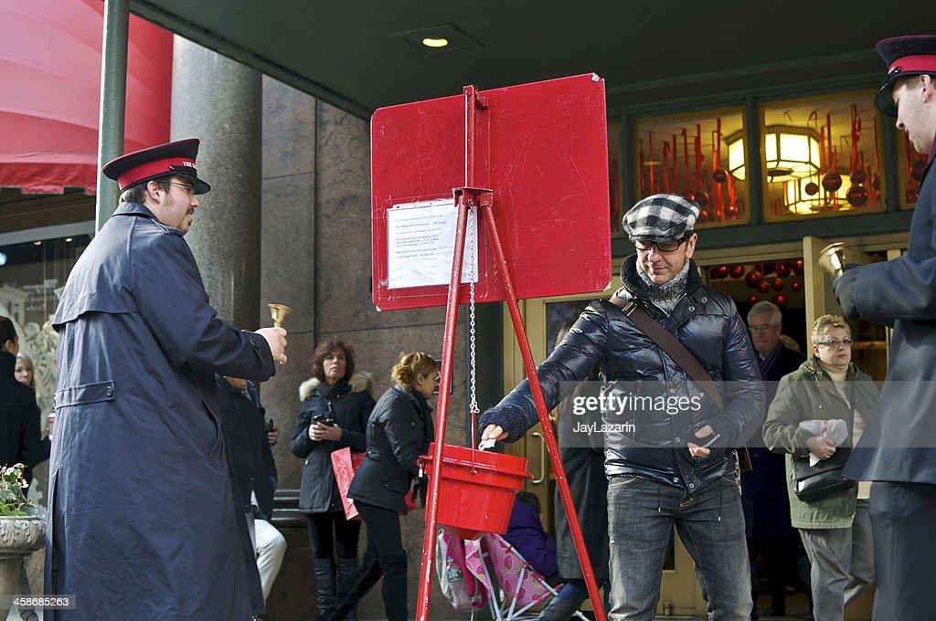 Man donating to Slavation Army Christmas bucket at Macy's, NYC : Stock Photo