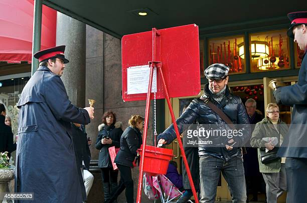 man donating to slavation army christmas bucket at macy's, nyc - salvation army stock photos and pictures