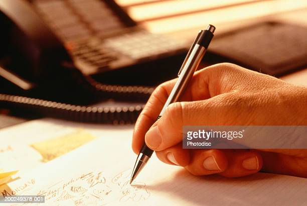 Man doodling with pen, Close-up of hand