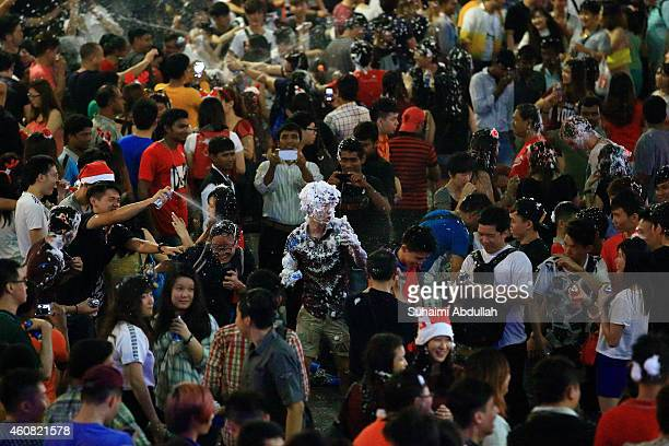 A man doused with snow spray is seen on Christmas eve at Orchard Road on December 24 2014 in Singapore Every year the famous shopping road is...