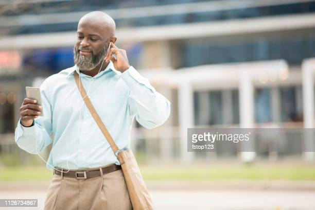 Man downtown using cell phone and earbuds.