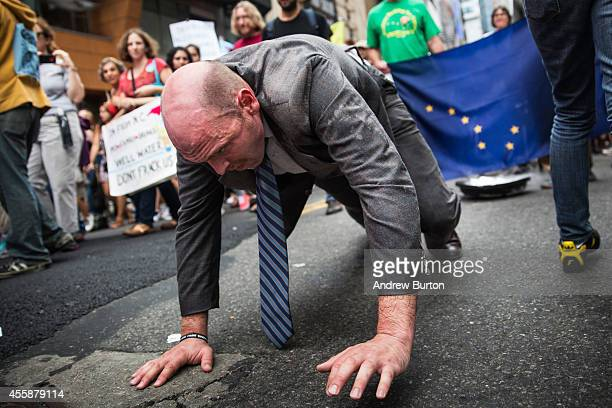 A man dragging a tray of dry ice in front of the Alaska state flag participates in the People's Climate March on September 21 2014 in New York City...