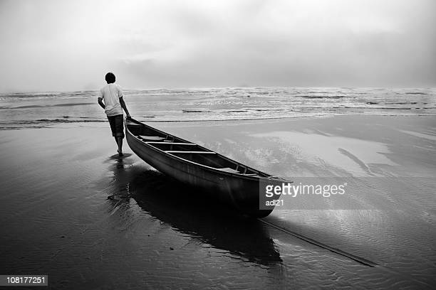 man dragging canoe boat into ocean, black and white - dragging stock pictures, royalty-free photos & images