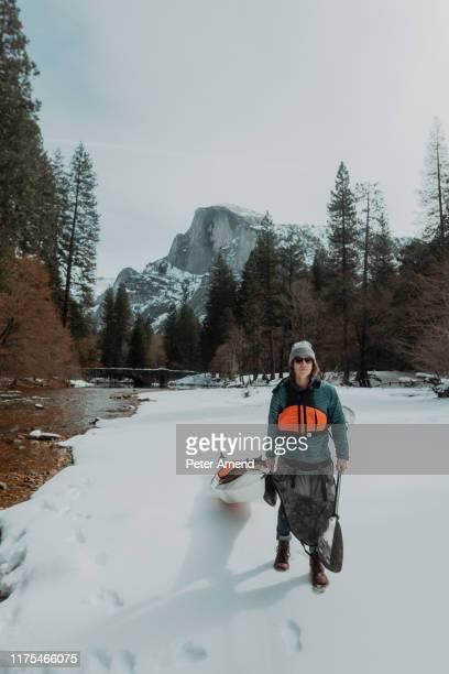 man dragging kayak across snow, yosemite village, california, united states - peter snow stock pictures, royalty-free photos & images