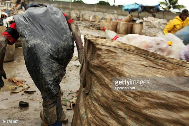 A man drags a bag of plastic bottles to be recycled at the Jardim Gramacho waste disposal site on December 9 2009 in Jardim Gramacho Brazil Referred...