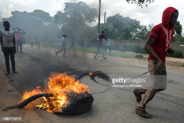 A man drags a burning tyre as angry protesters barricade the main route to Zimbabwe's capital Harare from Epworth township on January 14 2019 after...