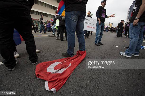 A man drags a flag of Turkey tied to his ankle as members of the ArmenianAmerican community and activists rally near the Turkish Consulate to...