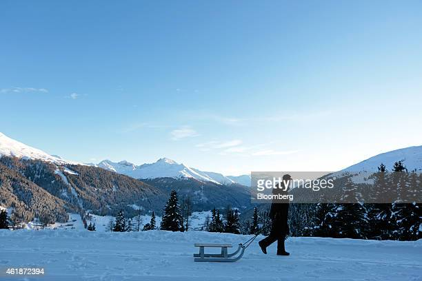 A man drags a toboggan through the snow on a mountainside ahead of the World Economic Forum in Davos Switzerland on Tuesday Jan 20 2015 This week...