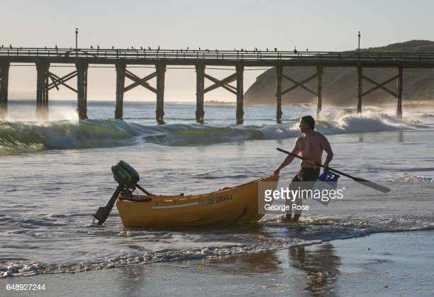 A man drags his small fishing boat out of the water and onto the sand at Gaviota Beach on December 28 in Gaviota State Park California Because of its...