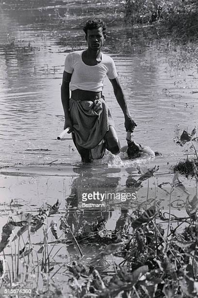 11/20/70 CHARJABBER PAKISTAN A man drags the body of a dead child who was killed in the tidal wave which hit this area Nov 12th and 13th US Army...