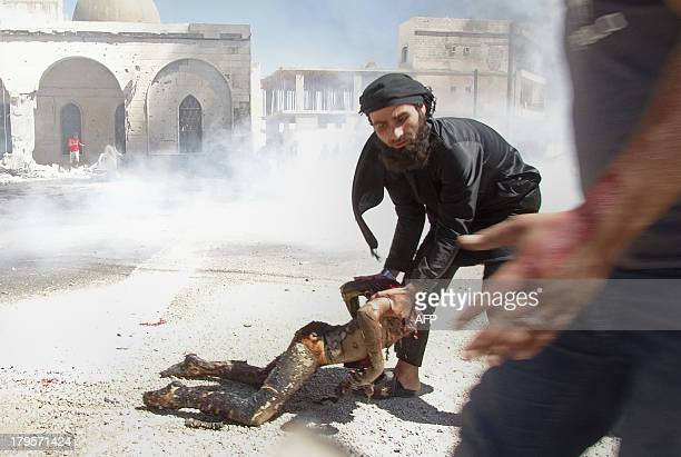 A man drags the remains of a beheaded charred body after reported air strikes by Syrian government forces in the rebelheld northwestern Syrian...