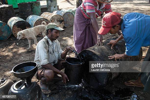 A man drains recycled oil from one of the 240kg drums into a pail on the banks of the Irrawaddy River on December 16 2013 in Yangon Myanmar Large...