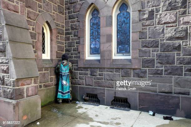 A man draped in a Eagles flag urinates as fans celebrate with the Philadelphia Eagles during their NFL Super Bowl victory parade on February 8 2018...