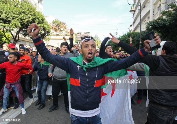 A man draped in an Algerian national flag chants slogans during an antigovernment demonstration in the capital Algiers on December 12 2019 on the day...