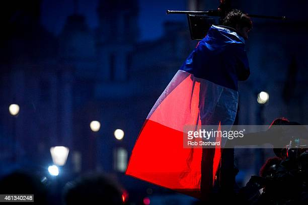 A man draped in the blue white and red colours of the national flag of France joins crowds gathered in Trafalgar Square paying tribute to the victims...