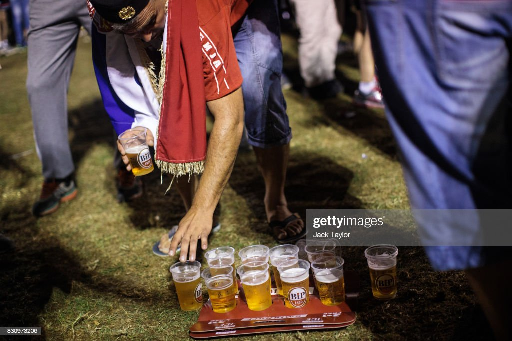 A man draped in the Serbian flag reaches for a beer by the main stage during the Guca Trumpet Festival on August 12, 2017 in Guca, Serbia. Thousands of revellers attend the trumpet festival, held annually since 1961 in the small, central Serbian town of Guca. The free event is a celebration of Balkan music with dozens of orchestras and solo trumpeters taking part in the festival's main competition. During the festival wild street parties take place throughout the night as brass bands parade and play for tips to the thousands of visitors in the town's restaurants, bars and pop-up tents.