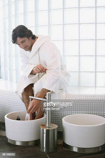 A man drawing a foot bath in a spa