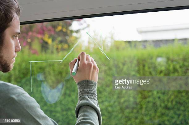 Man drawing an architecture design on the glass of window