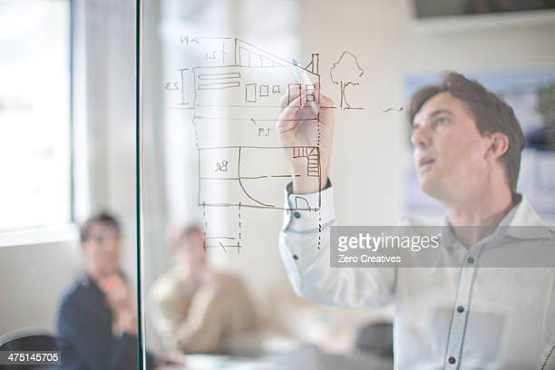 Man drawing architectural plans on glass wall, colleagues in background