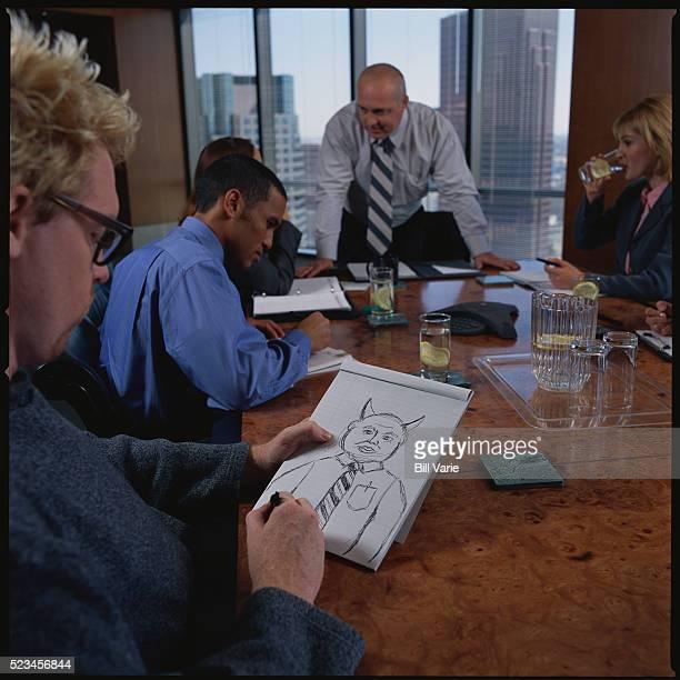 Man Drawing Cartoon of Boss at Meeting