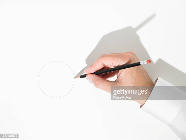 Man drawing circle with pencil, close up of hand, overhead view