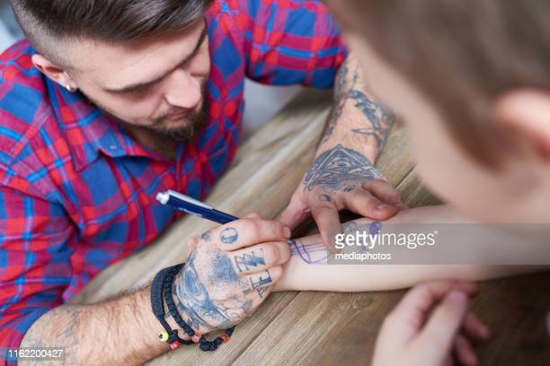 ペンでクールな入れ墨を描く男 - 臨時 ストックフォトと画像