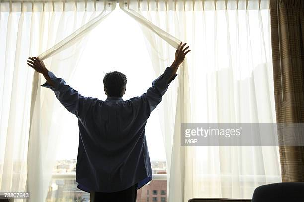 Man drawing curtains in hotel room