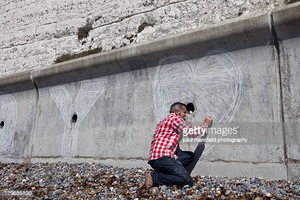 man drawing heaert shape with chalk - chalk wall stock pictures, royalty-free photos & images