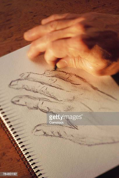 Man drawing his hand with charcoal