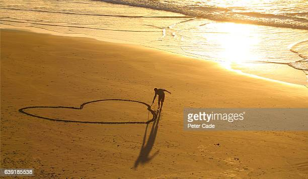 Man drawing large heart in sand on beach