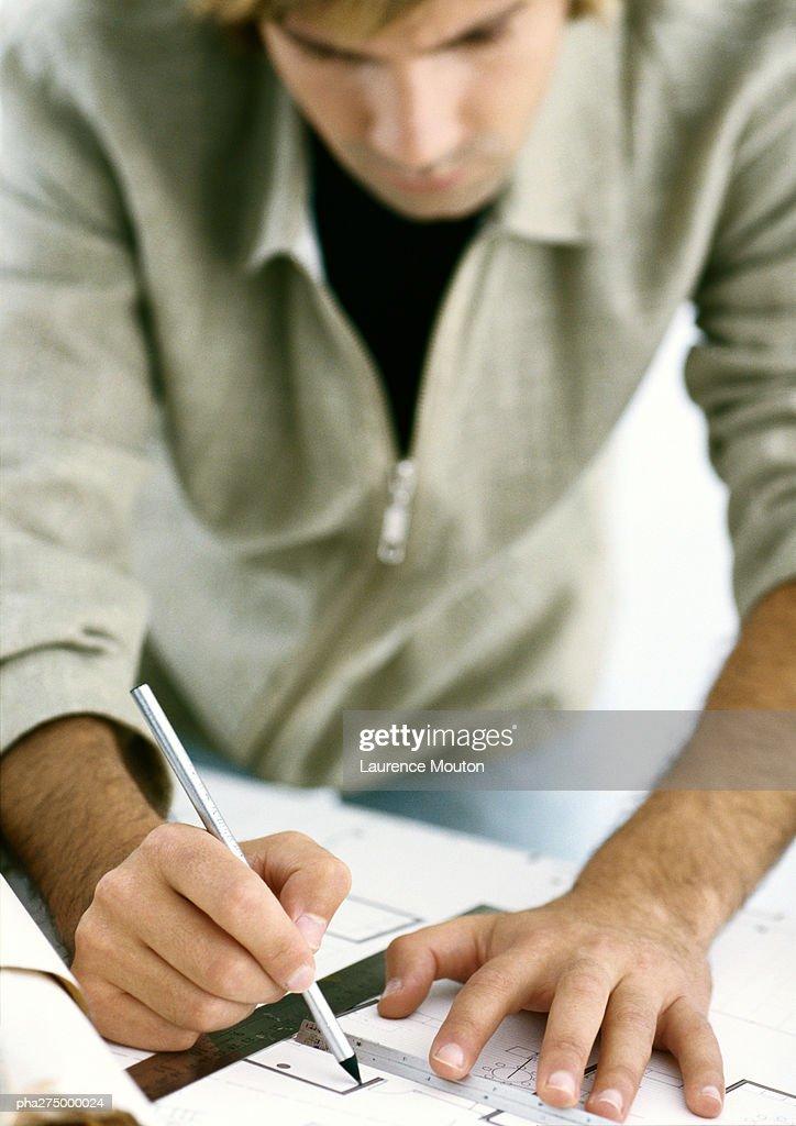 Man drawing on blueprints : Stockfoto