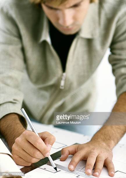 Man drawing on blueprints