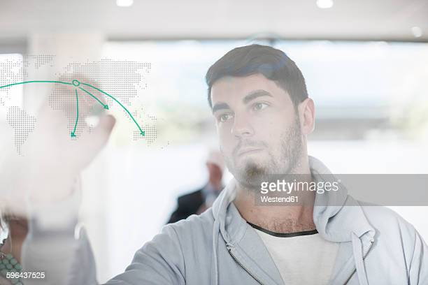 Man drawing on glass in office