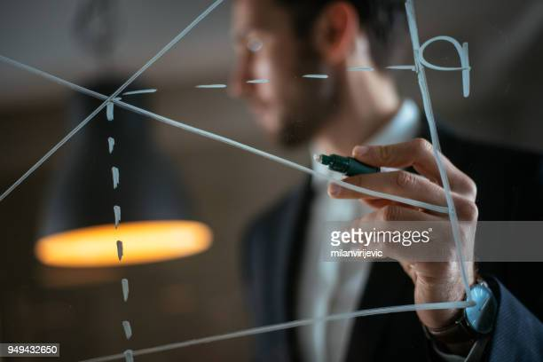 man drawing supply-demand chart on glass wall - managing director stock pictures, royalty-free photos & images