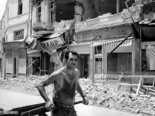 Man draws a cart in front of the damaged building after the Skopje earthquake circa July 1963 in Skopje, Yugoslavia.