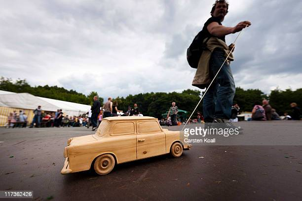 A man draws a carved wooden model trabant as fans and owners of East Germanera Trabant cars gather at the 2011 International Trabantfahrer Treffen on...