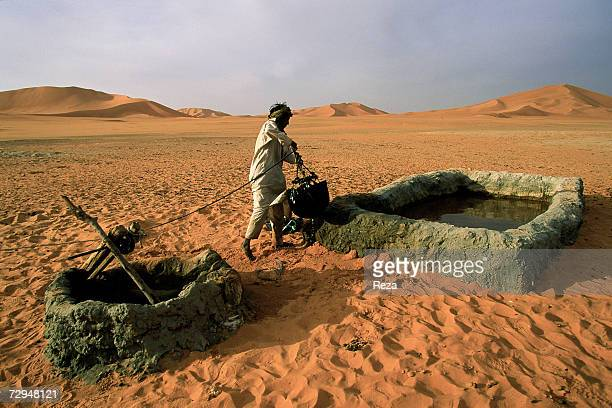 A man draws water in the middle of sand dunes in May 2000 in the Sahara Desert in Libya