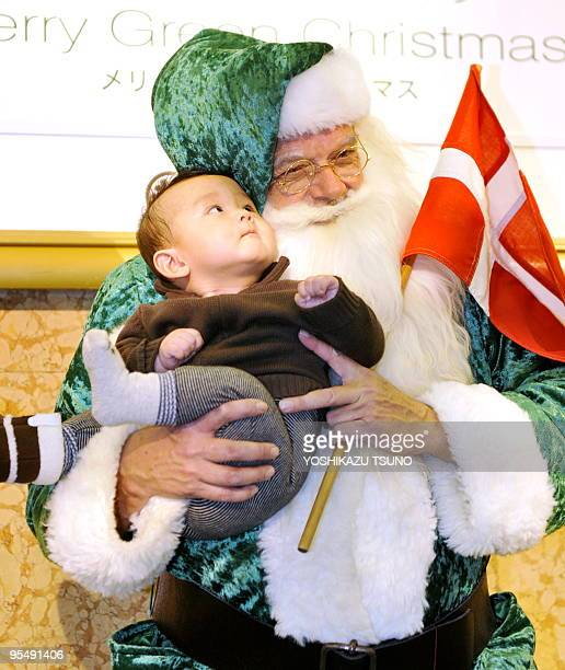 Man dreesed in a green Santa Claus suit carries a Danish flag as he holds a Japanese boy at the Mitsukoshi department store in Tokyo on December 5,...