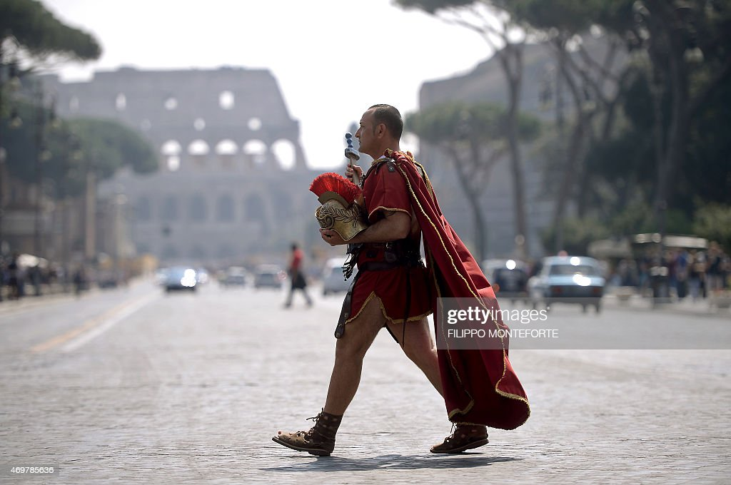 A man dressed as a ancient Roman centurion walks by the Colosseum in the center of Rome on April 15, 2015 FILIPPO