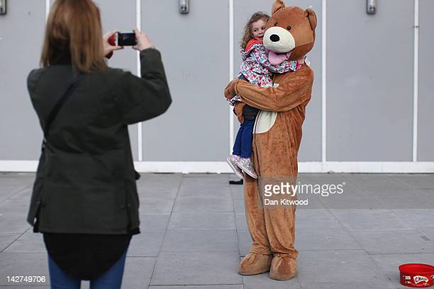 A man dressed as a bear poses for a photograph with a little girl on the South Bank on April 11 2012 in London England The South Bank which runs...