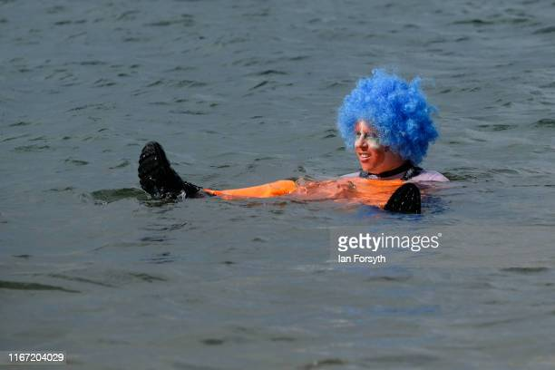 A man dressed as a clown floats in the water after falling overboard from his raft during a raft race at the annual Whitby Regatta on August 10 2019...