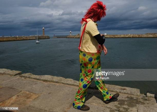 A man dressed as a clown walks along the harbour wall during the annual Whitby Regatta on August 10 2019 in Whitby England At over 170 years old the...