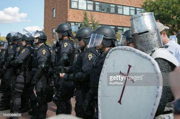 A man dressed as a Crusades knight stands with police during an open carry rally at Kent State University in Kent Ohio on September 29 2018