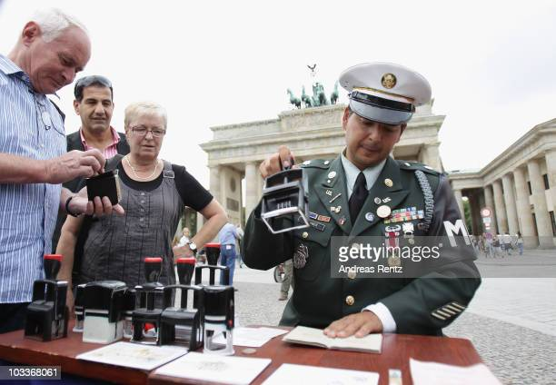 A man dressed as a former US soldier border offers to tourists to stamp their passports with visas with border passing stamps of the allied forces in...