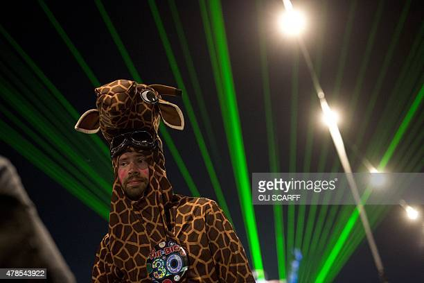 A man dressed as a giraffe stands in front of a laser light show in the 'Silver Hayes' area at the Glastonbury Festival of Music and Performing Arts...
