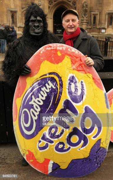 A man dressed as a gorilla and singer Billy Bragg pose with a poster of a giant Cadbury Creme Egg as they protest against the potential sale of...