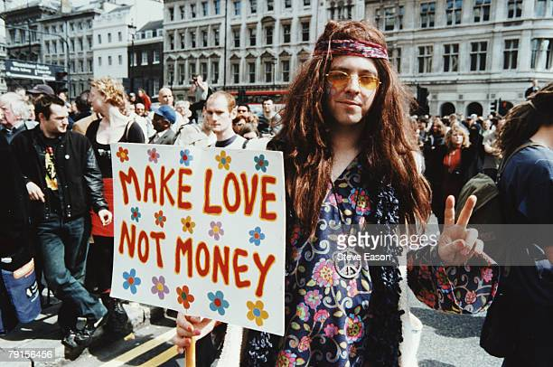 A man dressed as a hippy with a placard reading 'Make Love Not Money' at a Reclaim The Streets demonstration in London 1st May 2000