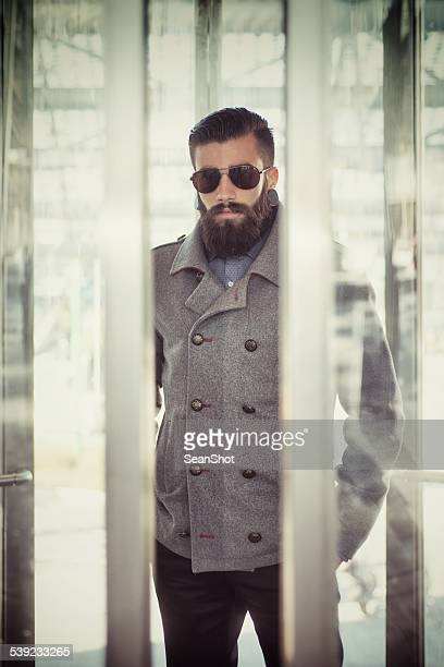A man dressed as a hipster rides in a glass elevator.