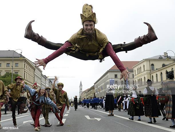Man dressed as a jester jumps during the traditional costume parade at the Oktoberfest beer festival in Munich, southern Germany, on September 20,...