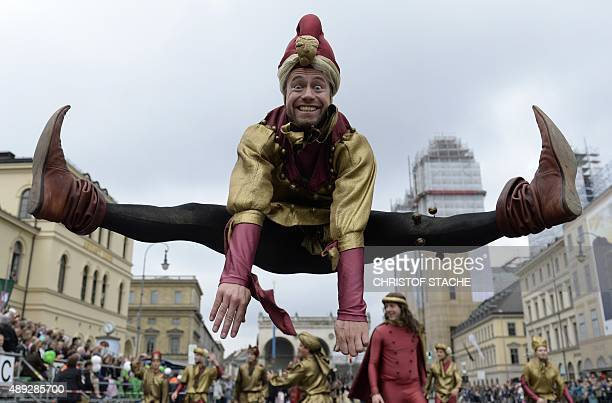 A man dressed as a jester jumps during the traditional costume parade at the Oktoberfest beer festival in Munich southern Germany on September 20...